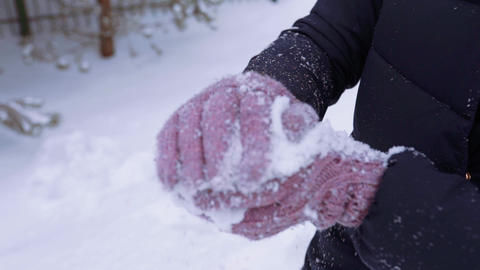 Woman in winter knitted gloves makes snowball and throws it, winter clothes Live Action