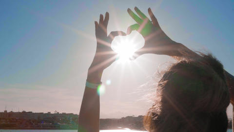 The girl from the hands made a heart shape at sunset, on the sea, against an Footage