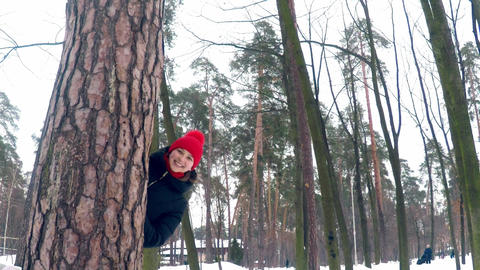 Young beautiful girl in a bright red hat with a big bambon looks out from behind Footage