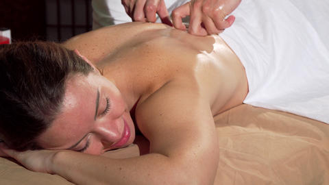 Attractive woman smiling with eyes closed, enjoying soothing back massage Live Action