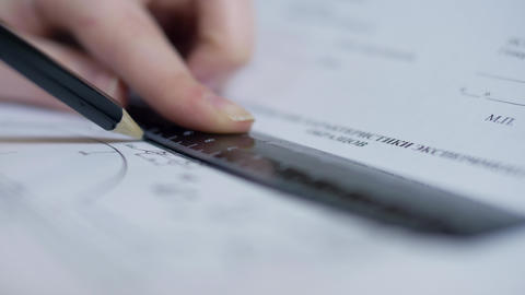 closeup woman designer holds ruler and draws straight line Live Action