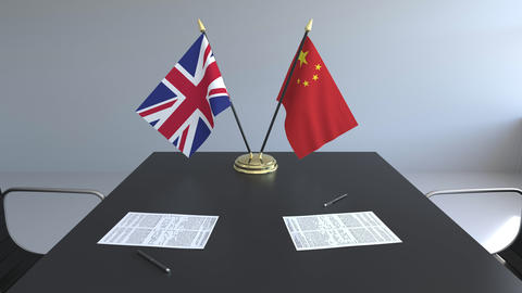 Flags of Great Britain and China and papers on the table. Negotiations and Live Action