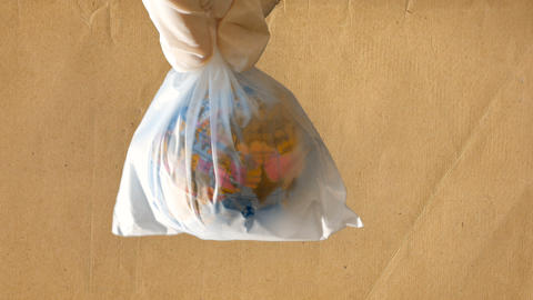 a teenage girl holds a plastic bag in her hand that contains a mini globe Footage