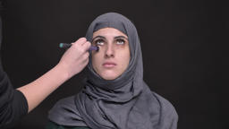 Portrait of female hands doing make-up for middle-aged muslim woman in hijab on ビデオ