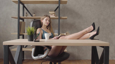 Portrait sensual woman in lingerie sitting in a black leather chair near shelf Footage