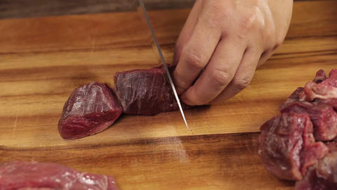 Raw Beef Piece - Being Cut Wth Knife Into Small Pieces - Front Angle 1 Live Action