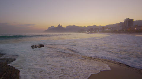 Waves rolling into Copacabana Beach as a woman walks in frame Footage