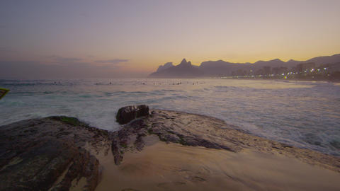 Slow motion, tracking shot of a surfer climbing rocks on Ipanema beach Footage