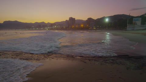 Slow motion pan of the tide coming in on Arpoador beach at sunset Footage