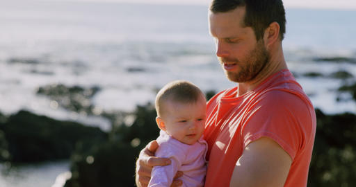 Side view of mid adult caucasian father holding baby at beach on a sunny day 4k Live Action
