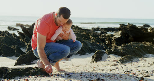 Front view of mid adult caucasian father holding his son and crouching at beach on a sunny day 4k Live Action