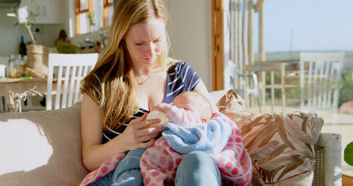 Front view of mid adult caucasian mother feeding milk her baby from bottle in a comfortable home 4k Live Action