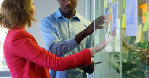 Mixed race business colleagues discussing over graph in modern office 4k Live Action