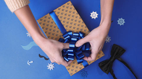 Gluing the bow to the present box for men, wrapping the present, parcel Footage