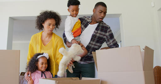Front view of black family unpacking cardboard boxes at comfortable home 4k Live Action