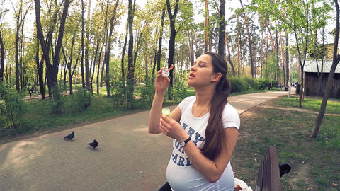 Young pregnant woman playing with soap bubbles in the park, Kiev, Ukraine Footage