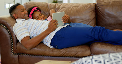Side view of young black father and daughter using digital tablet on sofa in a comfortable home 4k Live Action