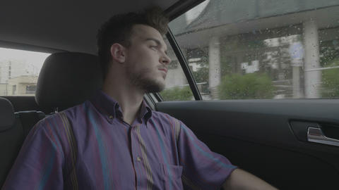 Melancholic young man dreaming and looking through the car window in his city Footage
