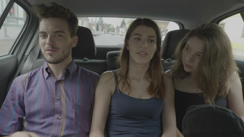 Millennial passengers friends talking and telling stories during traveling uber Live Action