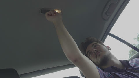 Bored teen man playing during road trip turning on and turning out the light of Footage