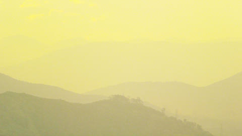 Pan shot of yellow fog over the mountains in Rio de Janeiro Footage