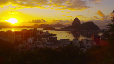Lens flare and large setting sun tracking shot over Atlantic Ocean and Botafogo  Footage