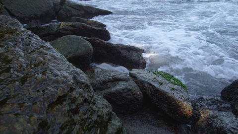 Waves crashing on shore rocks in slow motion Footage