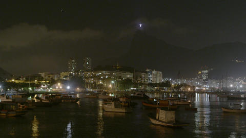 Sped up shot of a nighttime Rio across dark water Footage