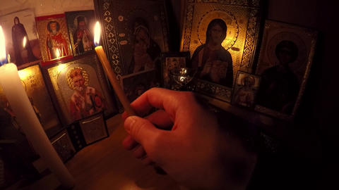 A person examines icons, highlighting candles Footage