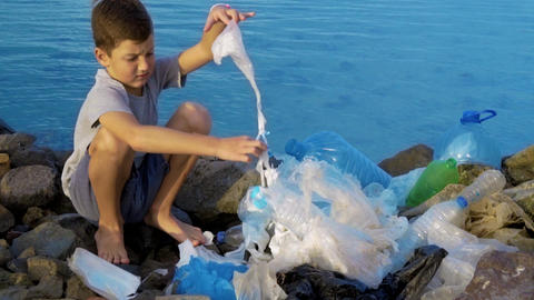 Litle child volunteer cleaning up the beach at the ocean. Safe ecology concept Footage
