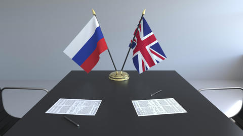 Flags of Russia and Great Britain and papers on the table. Negotiations and Live Action