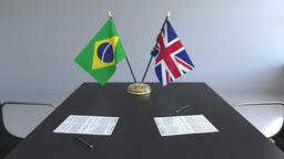 Flags of Brazil and Great Britain and papers on the table. Negotiations and Live Action