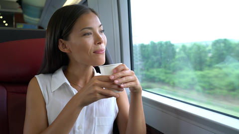 Asian woman traveling in train drinking morning coffee on commute to work Footage