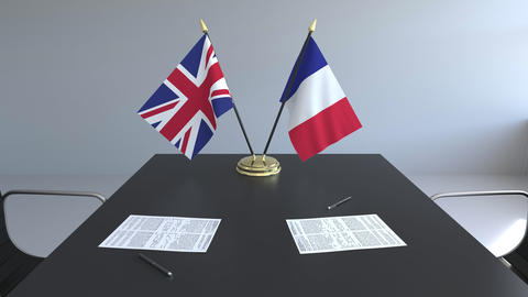 Flags of Great Britain and France and papers on the table. Negotiations and Live Action