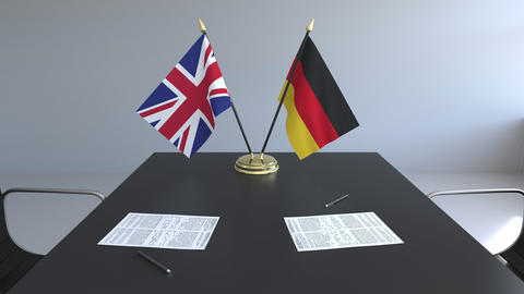 Flags of Great Britain and Germany and papers on the table. Negotiations and Live Action