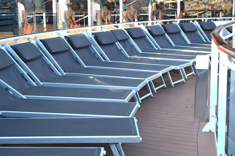 Empty sunbeds lounge chairs for relaxing on the open deck of a cruise ship フォト