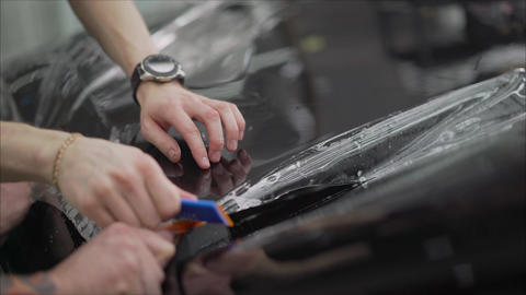 professional applying protective film to the red car. Master glues a protective Footage