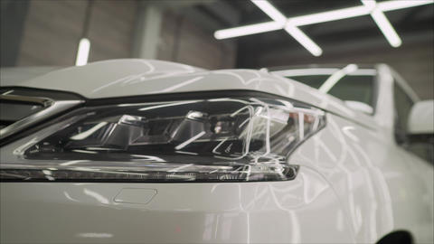 Headlight of an SUV close-up in a car-care center.. SUV Head Light white and Live Action