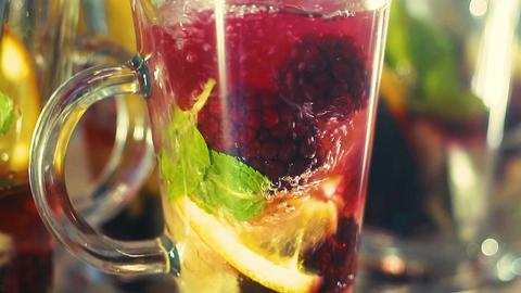 Tea in a glass, lemon, mint, orange, drops, spray, slow-motion shooting Footage