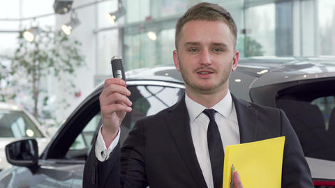 Professional car salesman holding car key, looking to the camera confidently Live Action