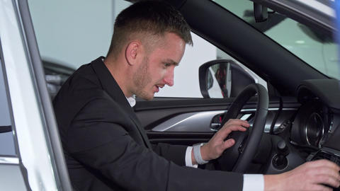 Businessman sitting in a new car, checking out interior of a vehicle Footage