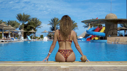 View from the back of a beautiful young tanned girl in an open swimsuit sits at Live Action
