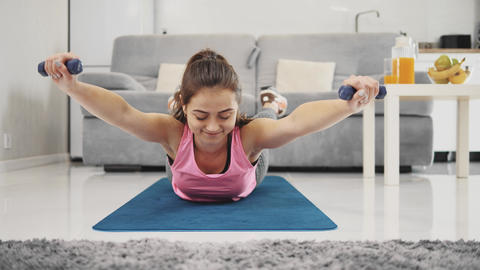 Young woman exercising at home in a living room ビデオ