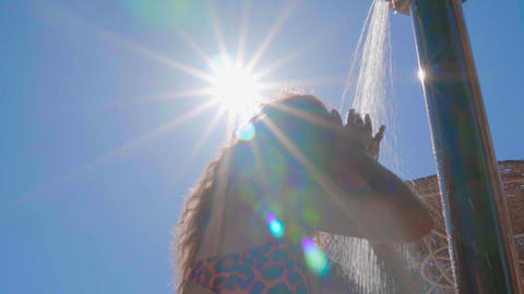 Woman has an outdoor beach shower with fresh water in slow motion on beautiful Footage