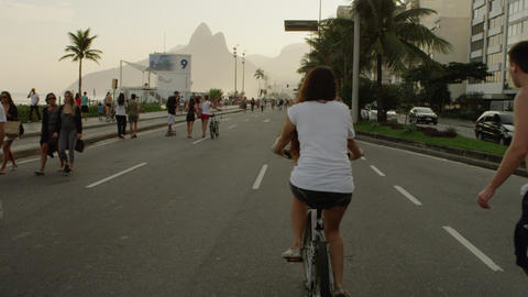 Slow-mo tracking shot of a girl on bicycle & a guy on skateboard heading dow Footage