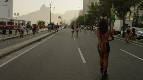 Slow motion tracking shot of a Brazilian girl rollerblading down Avenida Vieira  Footage
