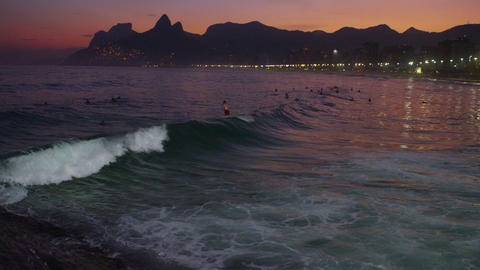Pan shot of sunset and rolling waves. People surfing, and Rio, Brazil lights in  Footage