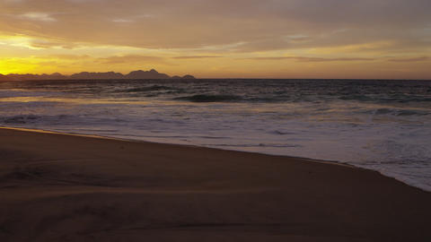 Slow motion, tracking shot across the sand as waves flow in on Praia do Diabo Footage
