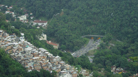 A paraglider flies over a city bluff overlooking a tunneled intersection in Rio  Footage