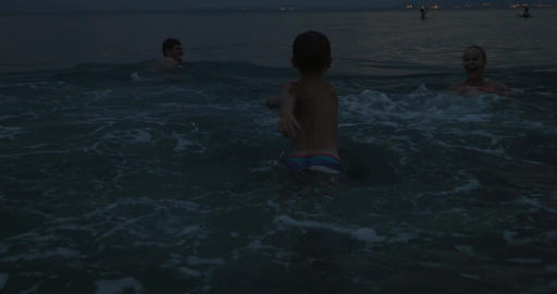 Family with child bathing in sea at twilight Footage